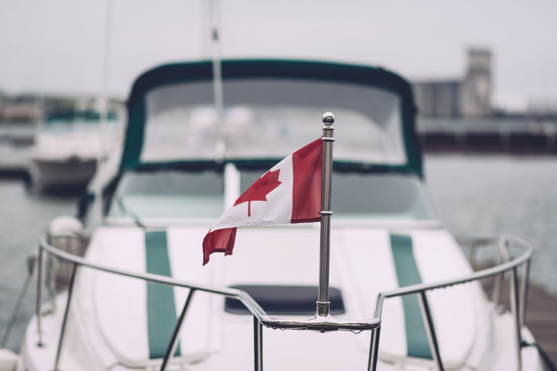 Marina Boat Close-up Day Dock Flag Focus On Foreground Harbor Independence Mode Of Transportation Moored National Icon Nature Nautical Vessel No People Outdoors Passenger Craft Patriotism Red Sailboat Sea Transportation Water