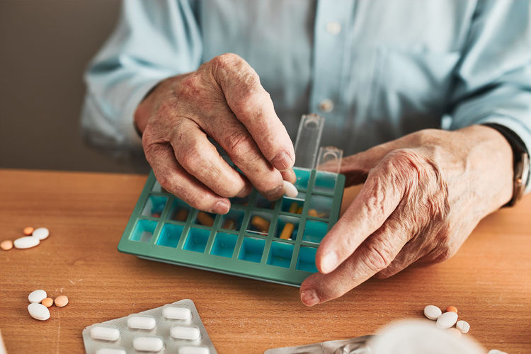 Senior man organizing his medication into pill dispenser. healthcare and old age concept
