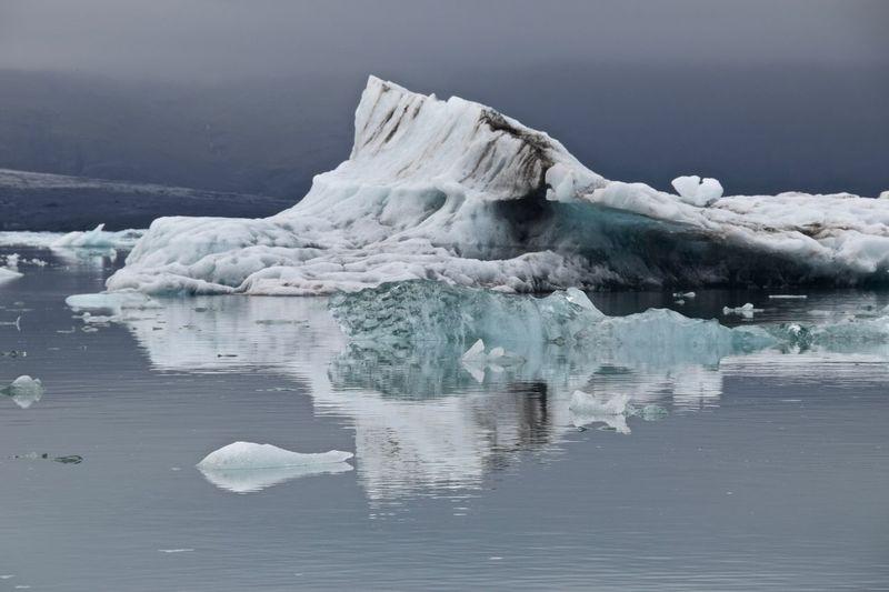 Glaciers in sea against sky