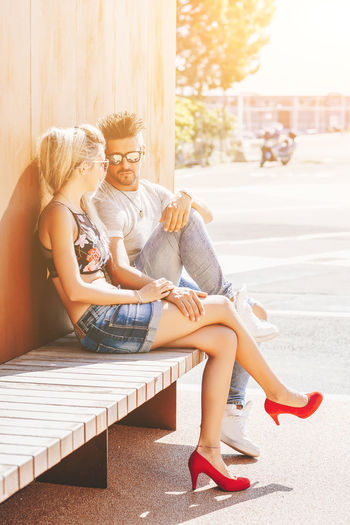 Mid adult couple sitting on boardwalk against wooden wall during sunny day