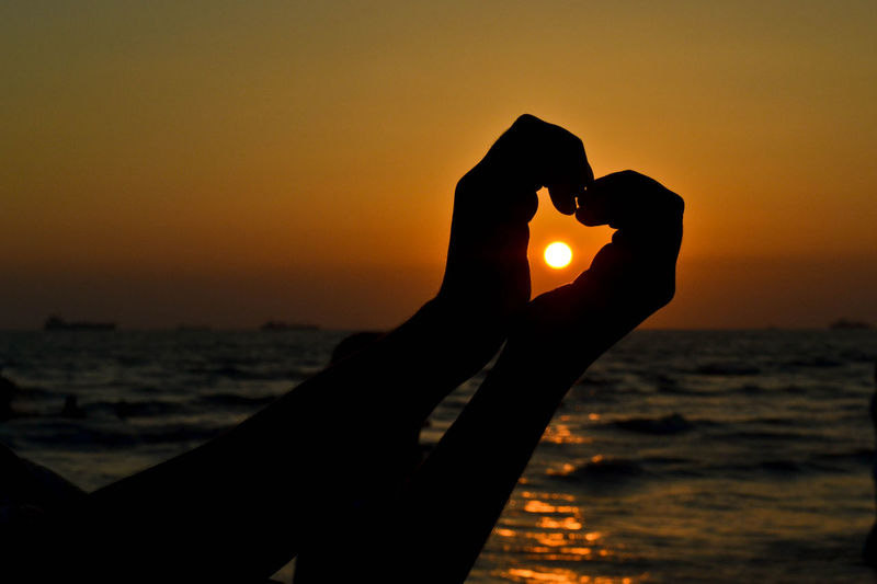 Close-up of silhouette hand making heart shape against orange sky during sunset
