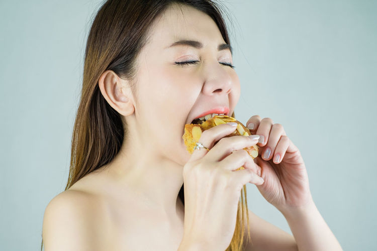 Close-up of woman eating food against white background