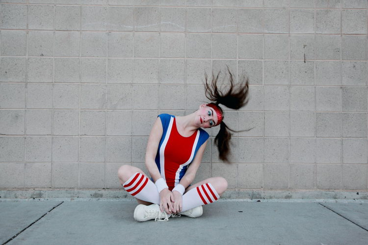 Woman In Sports Costume Tossing Hair While Sitting On Sidewalk Against Wall