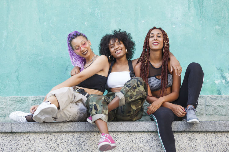 Smiling female friends sitting on retaining wall
