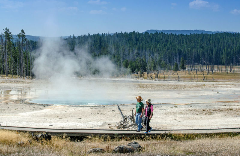 september 2017 Wyoming USA; tourists use safe walkways to view thermal hotsprings in Yellowstone National Park USA Tourist Attraction  USA Walkways  Yellowstone National Park Adult America Beauty In Nature Day Full Length Geothermal Activity Landscape Men Nature Outdoors People Sky Tourisim Tree Vacation