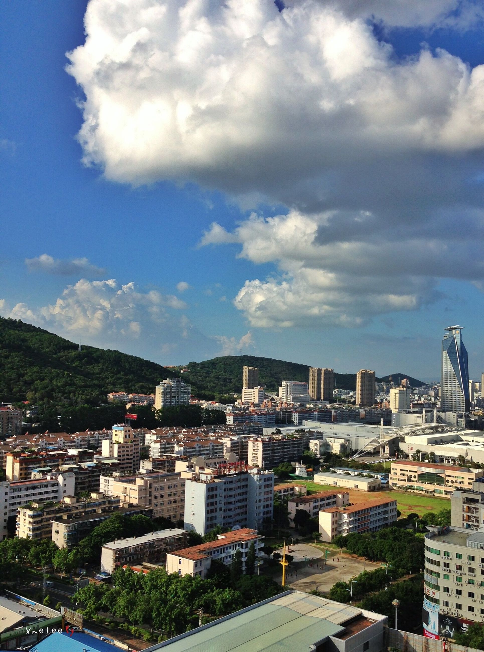 building exterior, architecture, built structure, cityscape, city, sky, cloud - sky, residential district, crowded, high angle view, residential building, cloud, residential structure, cloudy, mountain, blue, day, town, outdoors, city life