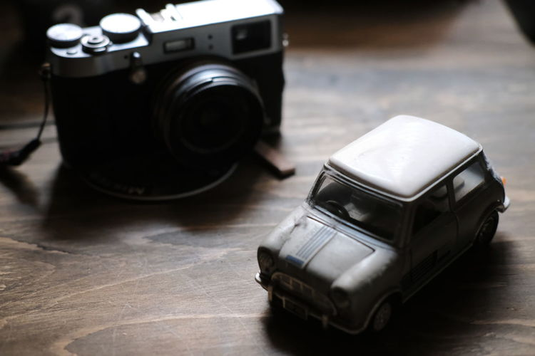 High angle view of toy car and camera on table
