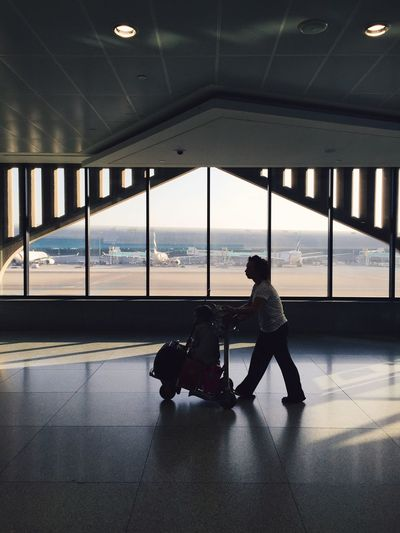 Woman walking with boy on luggage cart at airport