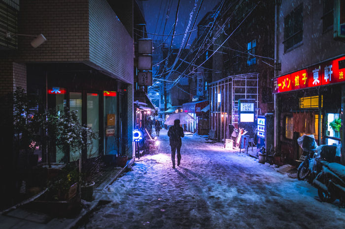 Rear view of person walking on illuminated street in city at night