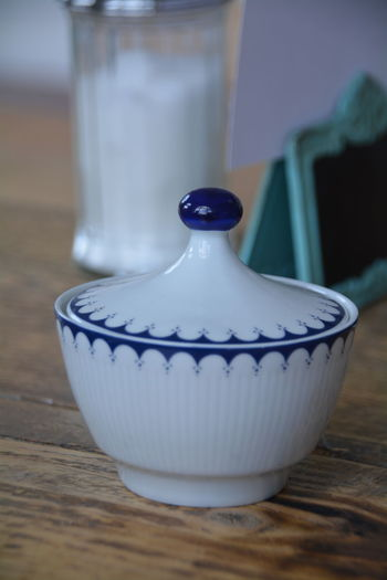 Close-up of white and blue ceramic container on wooden table