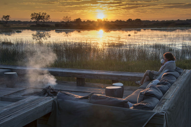 Woman drinking coffee on sofa against lake during sunset