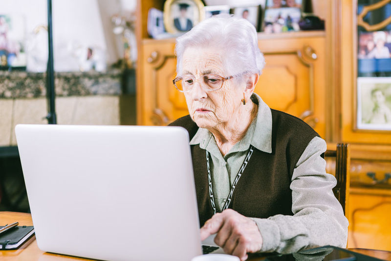 Senior woman surfing the net with a laptop at home. At Home Adult Casual Clothing Close-up Communication Computer Connection Day Eyeglasses  Gray Hair Indoors  Internet Laptop One Person People Retirement Senior Adult Senior Women Sitting Table Technology Using Laptop Wireless Technology