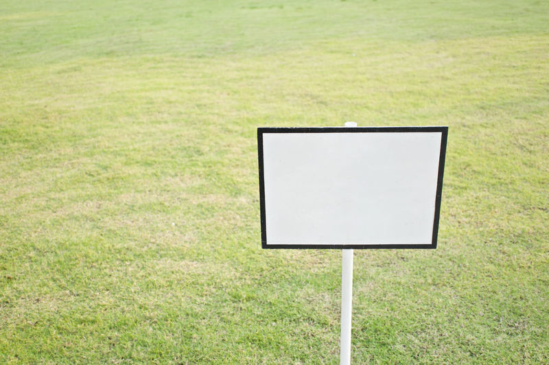 Empty black and white sign board on green grass in yard as background. Green Post Sign Banner Billboard Blackboard  Blank Copy Space Directional Empty Field Garden Grass Guidepost Information Lawn Nature Notice Noticeboard Park Placard Plant Private Public Yard