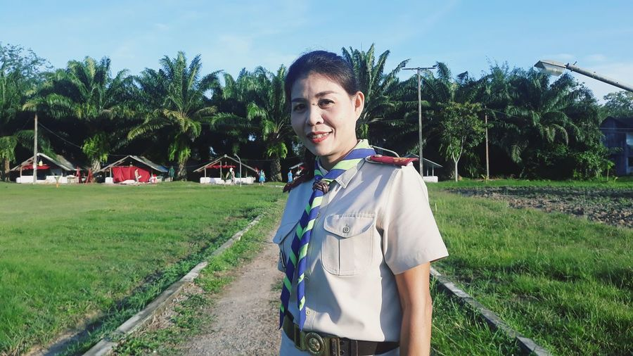 Portrait of woman wearing uniform while standing on field against trees