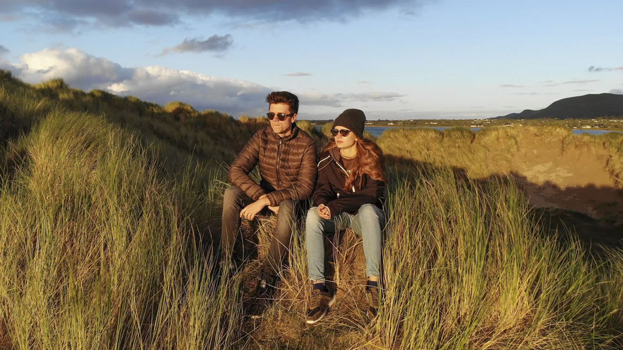 Young couple on land against sky