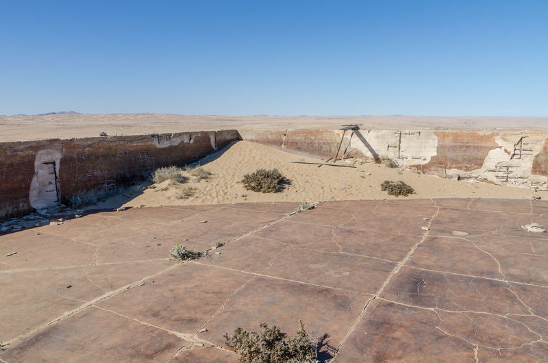 Scenic view of abandoned swimming pool at ghost town kolmanskop against blue sky, namibia