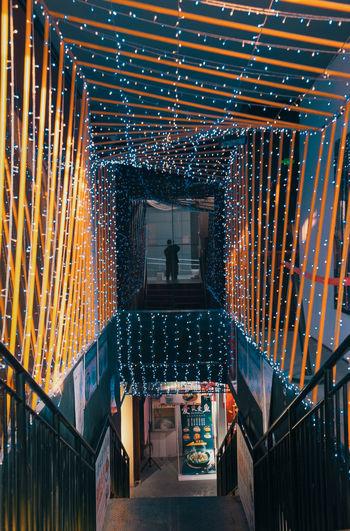 Rear view of man walking on illuminated building