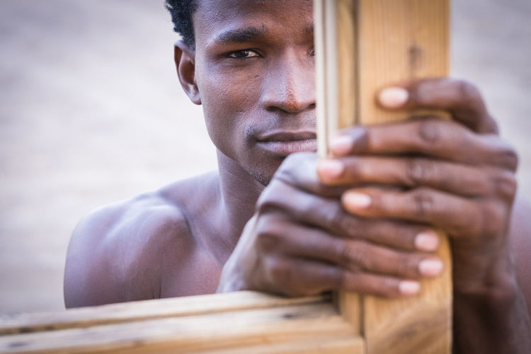 Fashion sensual black race ethnic african man take a wood bar and look to you with serious expression. young attractive model diversity skin and color. Beautiful portrait of male One Person Portrait Skill  Headshot Men Playing Close-up Music Holding Wood - Material Young Adult Looking At Camera Young Men Adult Artist Shirtless Musician 25-29 Years Leaning Hands Muscular Build Fingers Sunset Front View Attractive