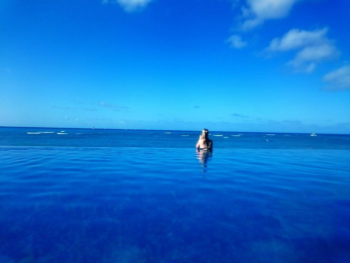 Rear view of woman in infinity pool by sea against sky