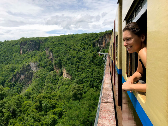 Train ride in Myanmar Woman Girl Train Train Ride Window Train Window Smiling Travel Adventure View Mountains Myanmar Real People One Person Leisure Activity Tree Lifestyles Plant Happiness Nature Rail Transportation Mode Of Transportation Young Adult Transportation Casual Clothing Green Color Looking Emotion Side View Females Outdoors