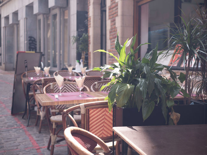 Empty chairs and tables at sidewalk cafe by building