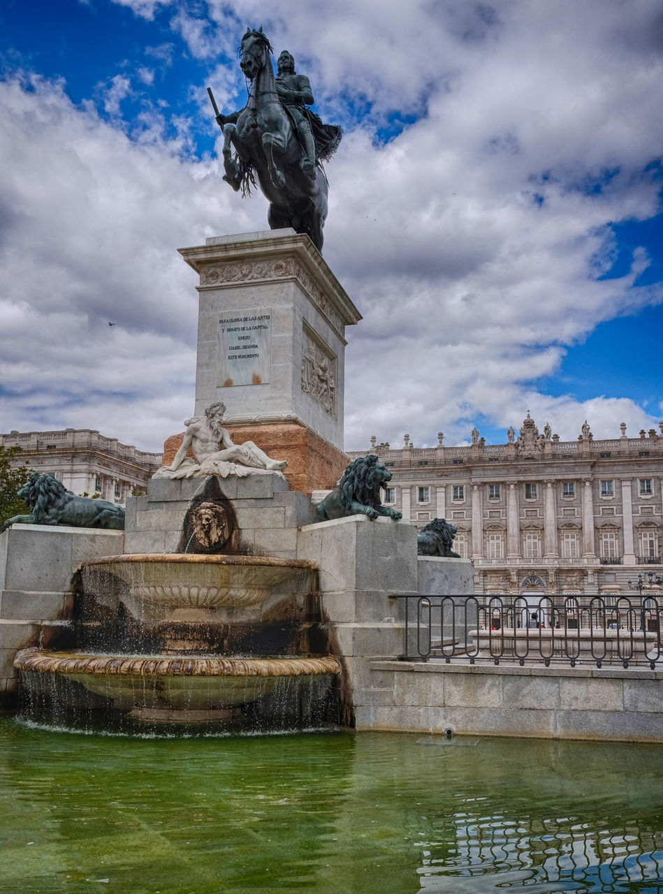 statue, architecture, sculpture, built structure, cloud - sky, sky, building exterior, water, human representation, waterfront, monument, outdoors, history, day, travel destinations, city, no people