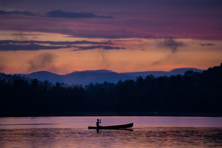 Silhouette man on boat sailing in lake against sky during sunset