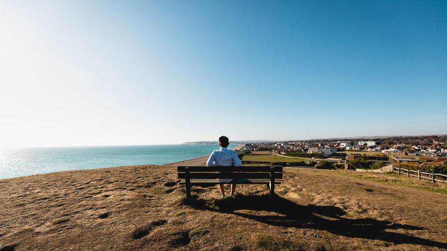 Rear view of man sitting on bench at beach against clear sky