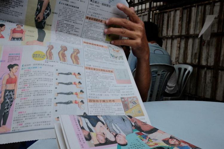 Man reading newspaper Relaxing Body Gesture Enjoying Life with Morningcoffee at Petaling Streeet Kuala Lumpur Malaysia