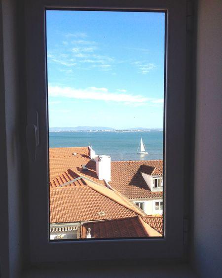 Sea against sky seen through window
