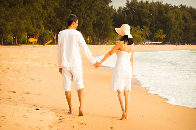 Happy couple walking hand in hand and barefoot on white sand beach. Couple in white costume ,woman with sun hat relaxing at sunset during vacation in phuket Family Andaman Sea Bare Foot Bride And Groom Engagement Photography Hand In Hand Marriage Ceremony Pine Tree Relationship Romantic Place Sea Sun Beach Side By Side Vacation Destination Valentine's Day