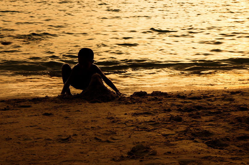 silhouette of people at the beach,The beauty of natural light at sunset. Land Real People Beach One Person Water Sea Leisure Activity Lifestyles Sunset Nature Sitting Sand Men Silhouette Vacations Sky Holiday Rear View Outdoors Silhouette Happiness Happy People Holiday Relaxing Children Women Man Romantic Orange Clouds And Sky Love Family Summer Sunrise Boy Freshair Freedom Fun