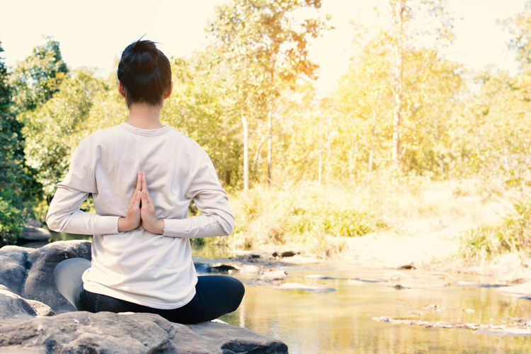 Rear view of woman practicing lotus position on rock by river