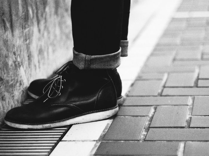 Low section of man leg in boots with rolled up jeans standing on pavement against wall