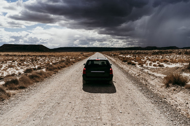 Cars on road amidst land against sky