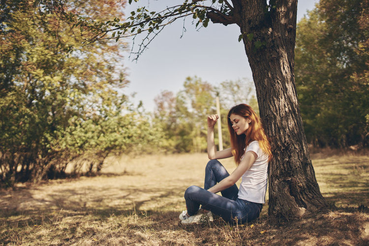 Portrait of smiling young woman sitting on tree trunk