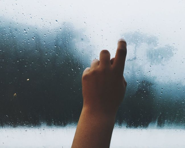 Cropped hand of person touching window with raindrops