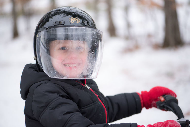 Portrait Of Boy Wearing Crash Helmet While Riding Bicycle During Winter