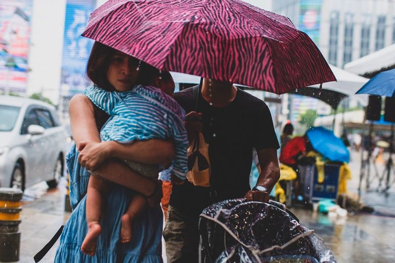 Rear view of man and woman in wet city during rainy season