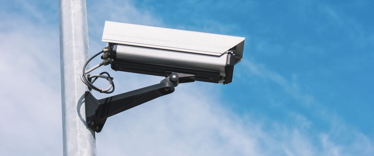 Low Angle View Of Security Camera Against Blue Sky