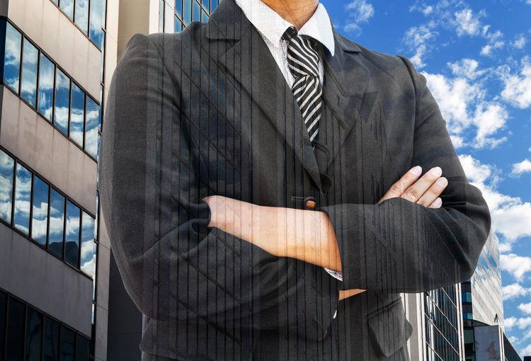 Digital composite image of businessman and building against sky