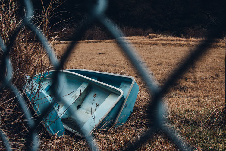 Beauty In Nature Simplicity Boat Faded Abandoned Fence Land Nature Field Day Plant Tree No People Focus On Background Chainlink Fence Transportation Grass Sunlight Mode Of Transportation Outdoors Barrier Damaged Protection Boundary 17.62° My Best Photo