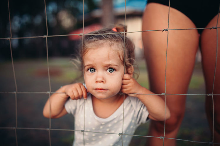 Portrait of cute girl standing by fence