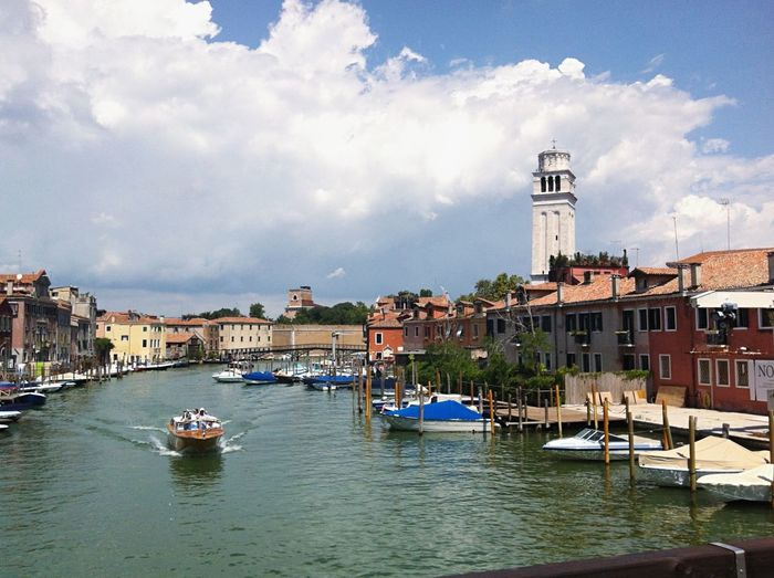 Buildings amidst grand canal against cloudy sky
