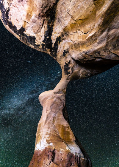 Low angle view of rock formations against star field
