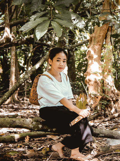 Portrait of woman sitting in forest