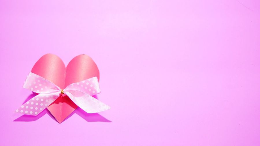 Close-up of heart shape made on pink background