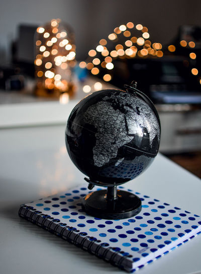 Close-up of globe and spiral notebook on table