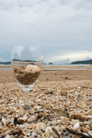 Close-up of wineglass on beach against sky