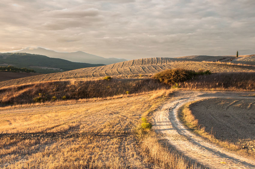 Another day begins in the Val D'Orcia Autumn Beauty In Nature Cloud - Sky Day Landscape Morning Mountain Mountain Range Nature No People Outdoors Road Scenics Sky Sunrise The Great Outdoors - 2017 EyeEm Awards Tranquil Scene Tranquility Tuscany Winding Road